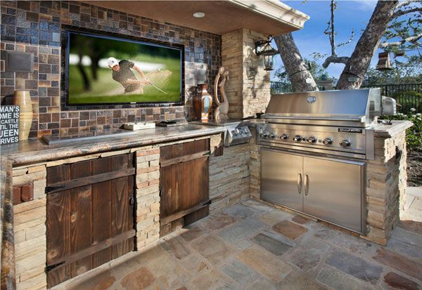 Image of a man cave outdoor kitchen with stone tile, flat-screen TV and multiburner grill