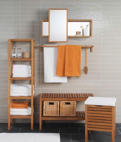 Rangement salle de bains brun clair dans une salle de bains carrelée de gris.