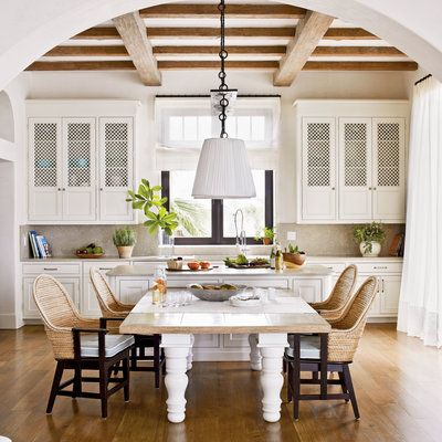 The neutral architectural elements in this kitchen—cement-cast walls and exposed ceiling beams—are reminiscent of white Grecian cottages, and the decor follows suit.