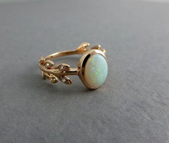 Beautiful leaf opal engagement ring. This leaf ring has 6 leaves on either side of the opal. There are no leaves on the back of the ring. It is