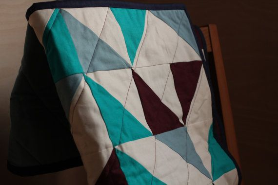 This quilt measures 28 x 36 (71cm x 91cm).  The top is made from high quality cotton fabric in burgundy, teal, duck egg blue and ivory, arranged
