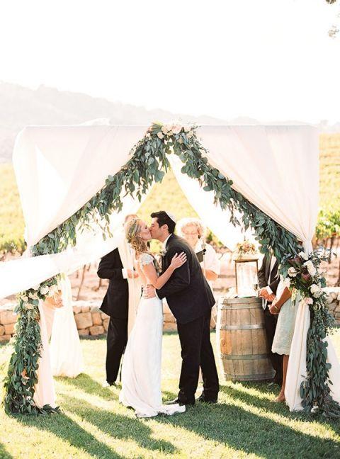 Wedding Ceremony with Greenery Garlands and White Drapery | Danielle Poff Photography | http://heyweddinglady.com/natural-elegance-southern-california-vineyard/