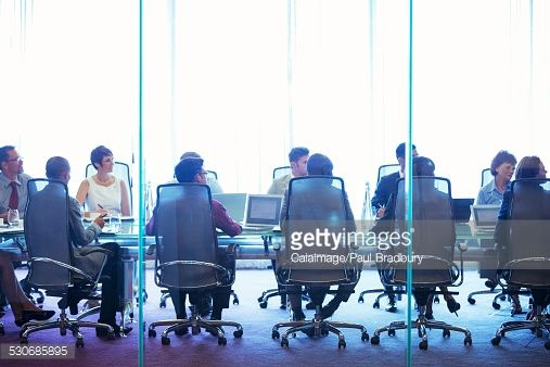Stock Photo : Business people having meeting in conference room, sitting with laptops and discussing