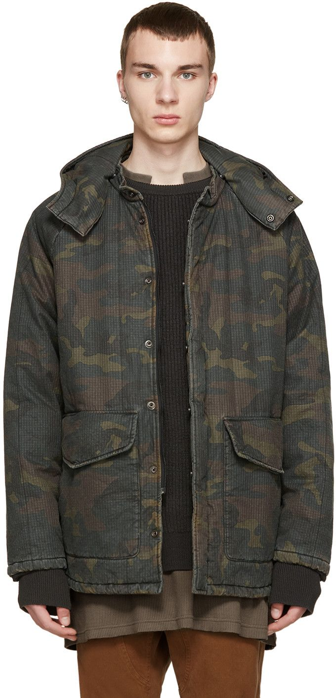 Long sleeve quilted canvas coat featuring a camouflage pattern throughout in tones of brown and green. Lightly padded throughout. Detachable hood with press-stud fastening at collar and throat. Zip closure at front concealed by press-stud placket. Flap pockets with press-stud fastening at waist. Fully lined. Tonal stitching.  This item has gone through a unique dyeing and cutting process. Please note that finishings may vary.   Part of the adidas Originals by Kanye West YEEZY Season 1.
