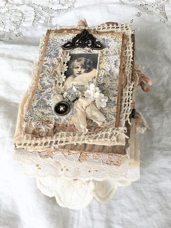 Believe... This gorgeous heirloom journal is a one of a kind beauty handmade from corrugated card, old book pages, many vintage and new items such as eyelet, laces and fabrics. Embellished withTim Holtz assemblage rhinestone, metal embellishment, vintage buttons, vintage forget-me-nots (not reproduction) vintage image and the word believe cut from an old book. Contents include 32 pages consisting of papers from the Tim Holtz Memoranda paper stack, vintage book pages, tea dyed tracing and…