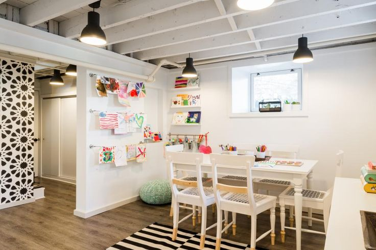 Designer Justine Sterling transformed a low-ceiling basement space in a 1920s Colonial to create a studio. It's a walkout basement with two windows providing decent light, but it was very ugly with exposed pipes, a horrible acoustic tile ceiling and old sticky vinyl flooring. At roughly 450 square feet, there was a good amount of space to create a project room for the children. The room is now a lively children's workspace.