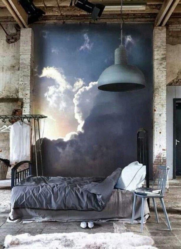 Bed met blauw dekbedovertrek in oude fabriekshal, retro industriële hanglamp, kledingrek en muurschildering.