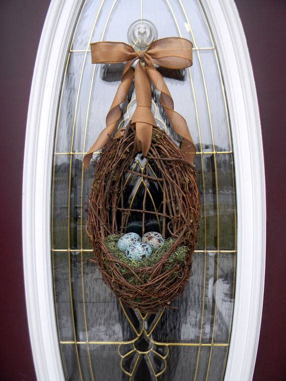 Easter/springtime wreath. Oval grapevine wreath with a basket area and filled it with spanish moss and 3 blue eggs speckled in brown. Brown/tan burlap ribbon for a final touch.