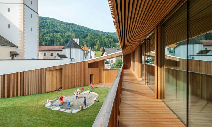 Austrian architects feld72 to have unveiled a new kindergarten building located in the small village of Valdaora di Sotto in South Tyrol. The elongated timber structure holds court in the mountainous region, encased by a solid wall and tucked into the hilly landscape.