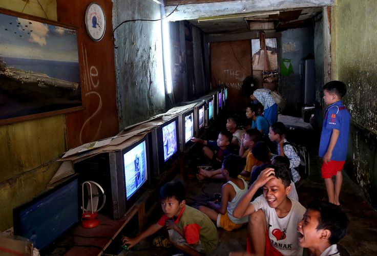 Indonesian young boys play video games at its rental house where people can rent video game consoles with U.S. 3 cents per-hour, in Jakarta, Indonesia, Aug. 25. (Tatan Syuflana/Associated Press