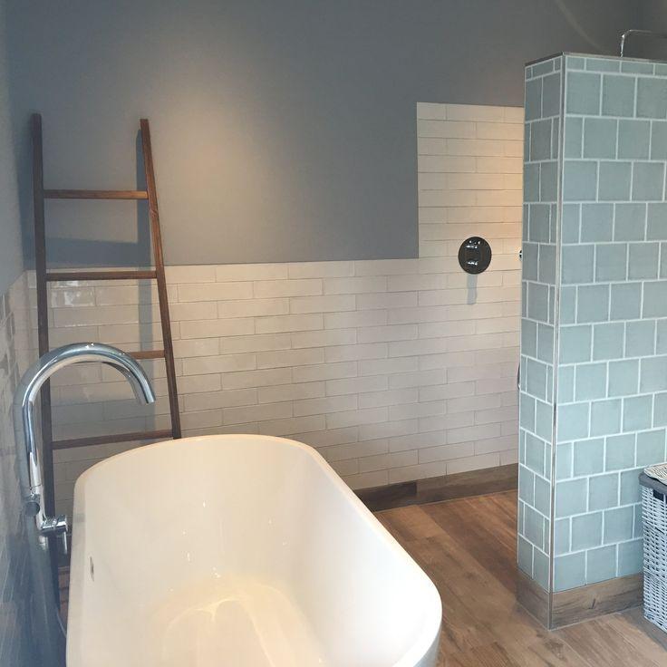 Prachtige modern landelijke badkamer met planken tegels op de vloer, vrijstaand bad, sfeervolle handvorm wandtegels in groen en wit en prachtige inloopdouche met inbouw kranen