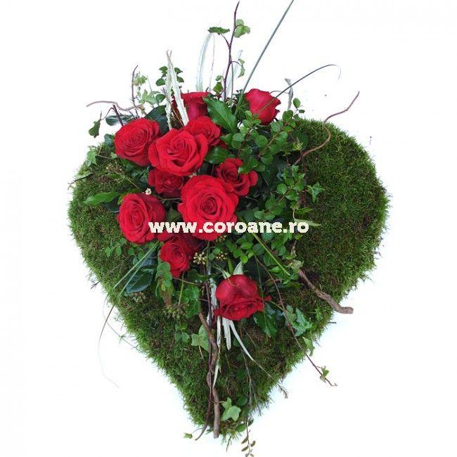 Comanda online aceasta inima funerara realizata din muschi natural si decorata cu trandafiri rosii, verdeata proaspata si ramuri de copac naturale.