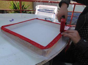 3. Mojar muselina y ponerla sobre el marco de madera (aproximádamente 40×40 cm). Proceder a engrapar la tela desde la parte superior con una cinta ancha en los bordes, tirando siempre en la dirección contraria a donde se están poniendo las grapas. Cuidar que la tela quede con una tensión adecuada en todas las direcciones.