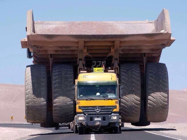 A Mercedes-Benz Actros truck transporting a giant mining haul truck over a local road. Unknown photographer and location.
