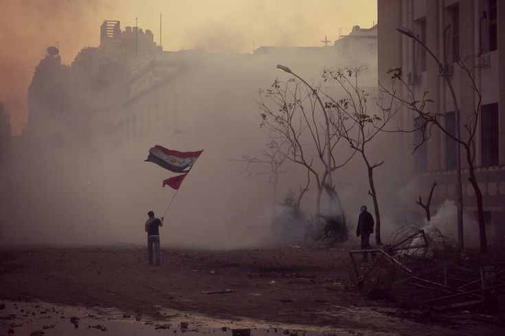 Dusk 4 February 2012. A protester defiantly waves an Egyptian flag with the emblems of Christianity and Islam (the cross and the crescent) added - a message of religious unity.    Clouds of tear gas  in the background are lit up by with an eerie glow by the sinking sun.  He is actually standing in Mansour Street near to the junction of Mohammed Mahmoud in Downtown Cairo. The flag waver was said to have been a relative of one of the Christian demonstrators who died at Maspero in October…