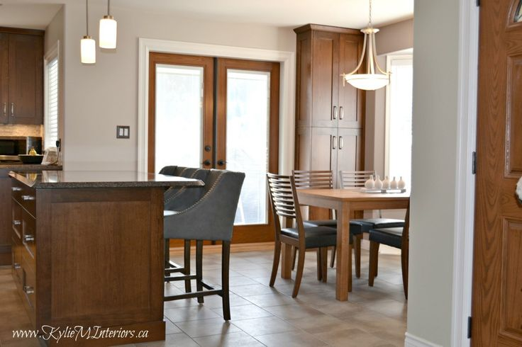 open layout kitchen and dining room with island, quartz countertops and benjamin moore abalone and sandlot gray with purple travertine backsplash