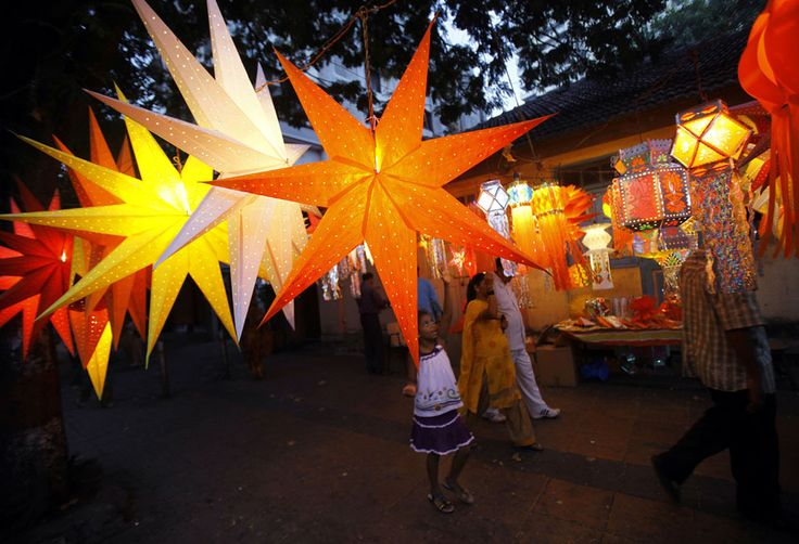 An Indian girl tries to reach a lantern displayed for sale at a roadside stall ahead of Hindu festival of lights Diwali, in Mumbai, India