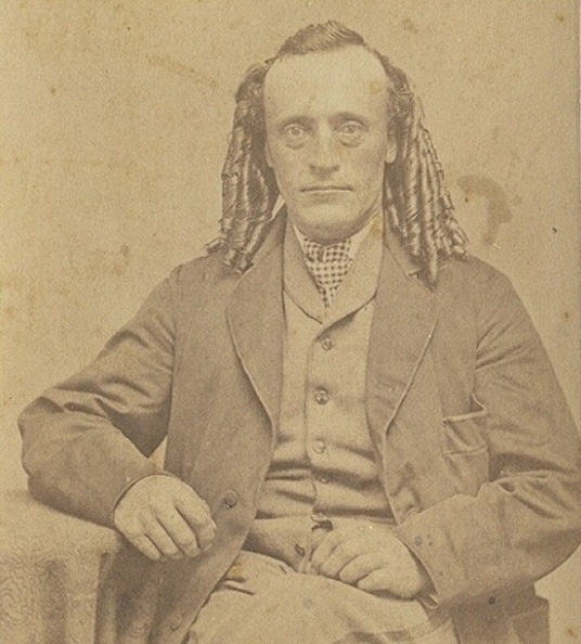 1800s looks like a man sporting a ladies hairpiece ?