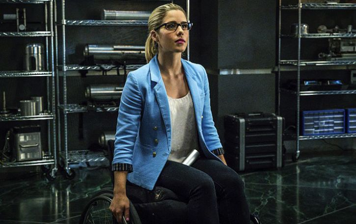 Emily Bett Rickards as Felicity Smoak sits in a manual wheelchair with her hands on the wheels. She is wearing a white shirt under an open blue shirt/jacket, and glasses and seems to be in a room with tech gear behind her  Feb.19, 2016
