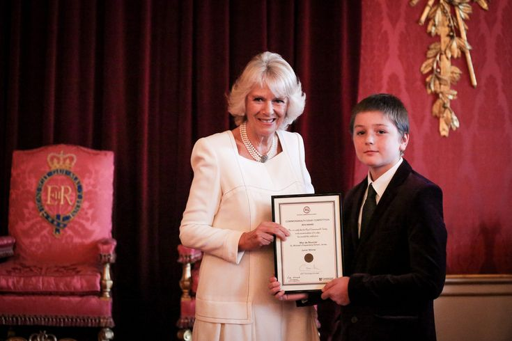 Camilla, Duchess of Cornwall presents Max de Bourcier, 10, Junior Winner from St Michael's Preparatory School, Jersey with his award during a reception for the winners and runners up of The Queen's Commonwealth Essay Competition 2015 at Buckingham Palace on November 19, 2014 in London, England