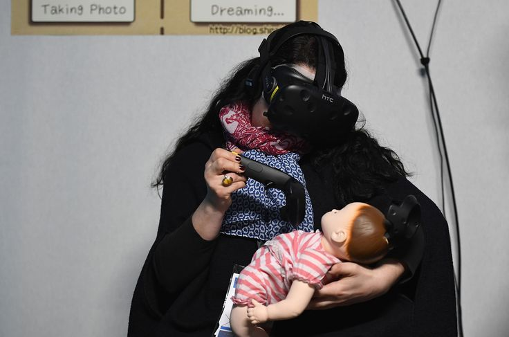"A visitor simulates nursing a baby while wearing a Virtual Reality headset during the ""Laval Virtual"" virtual reality, augmented reality, and 3D techonology show on March 22, 2017, in Laval, western France."
