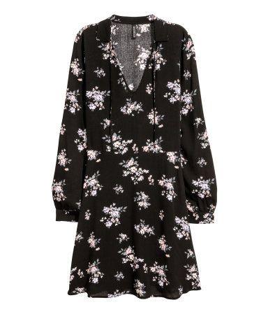 Sort/Blomstret. Kjole i crinkled, vævet viskose med trykt mønster. Kjolen har V-udskæring med krave og bindebånd i halsudskæringen. Lange ærmer med manchet