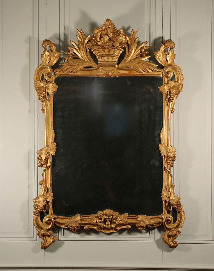 BrochureMiroir en bois sculpté et doré, production provençale d'époque Louis XV. Sur le fronton, un panier rempli de grappes de raisins est encadré de feuillages. Aux angles, des enroulements sont surlignés d'acanthes et de raisins. Les montants sont décorés de pampres également. La traverse inférieure est enrichie au centre d'un bouquet de fleurettes. Ce miroir …
