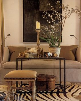 """Chic Living Room: I love the effect of that light """"artsy"""" flowering plant against the large dark piece of art in the background. That and the animal print rug really make this room."""