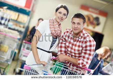 Young Family couple with trolley cart in meat grocery supermarket during weekly food shopping