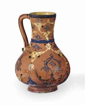 AN IZNIK POTTERY JUG OTTOMAN TURKEY, CIRCA 1570 Of accentuated baluster form with large belly, the dusty pink slip ground covered with blue slip arabesque panels enclosed within white arabesque ogival lattice, between plain blue bands, mouth restored 9¼in. (23.4cm.) high