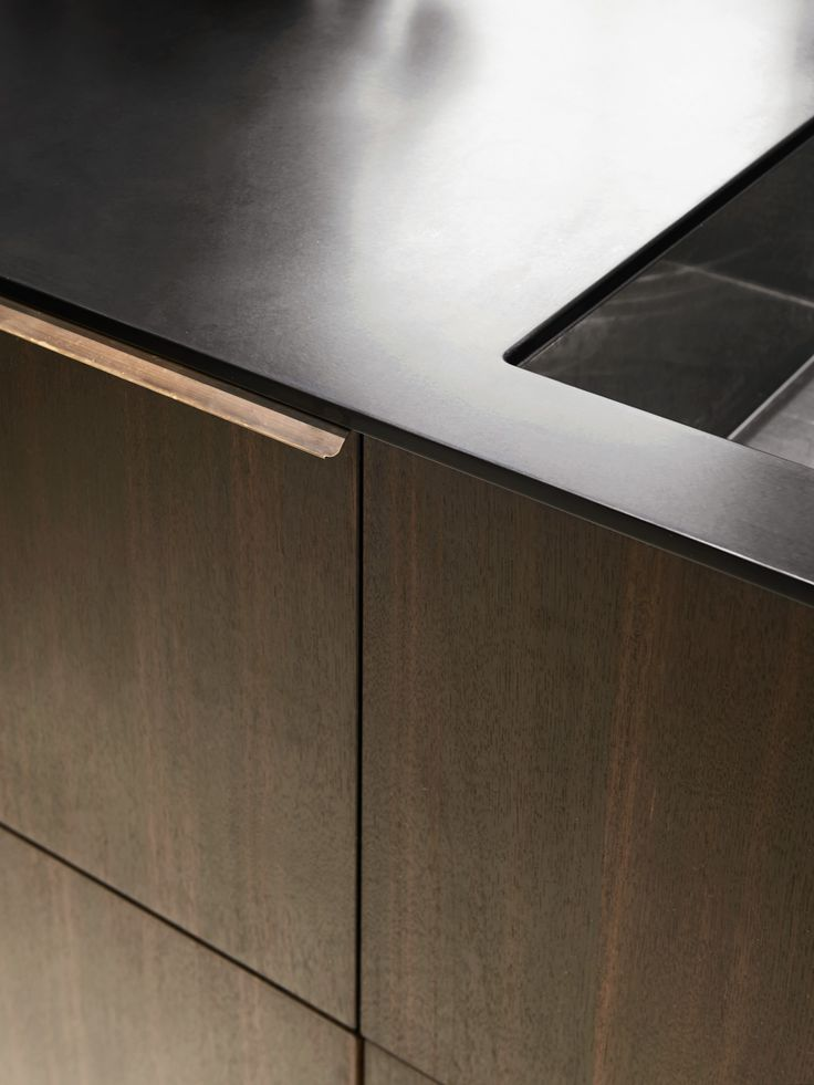 Reform's Norm Architects' kitchen design in sawn smoked oak, bronzed tombac handles and countertop in black corian.
