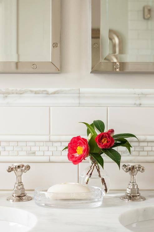 A double vanity with white marble countertops boasting polished nickel hardware sits below two polished nickel vanity mirrors hanging on off-white walls accented with a white marble chair rail, white subway tiles, marble pencil tiles, and white marble mosaic accent tiles.