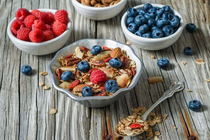 """Homemade healthy coconut granola and berries in small bowl, strawberries, blueberries, goji berries, nuts. Healthy lifestyle.: """"Snacks that are very high in carbohydrates can elevate blood glucose levels too much before the next meal."""""""