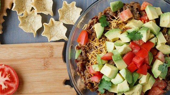 Layers of spicy sausage, beans and rice, shredded cheese, and guacamole make a delicious Cajun-inspired dip for tortilla chips.