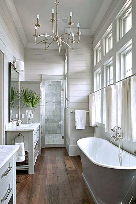 wood flooring and tile shower. calming colors, and I like how that shower stall is positioned, plus the pretty bathtub by the curtained windows