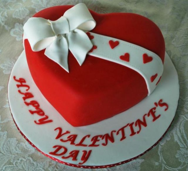 Red heart shaped valentine cake with white cake bow.PNG