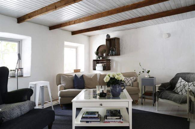 Soffan och den svarta stolen är från Bröderna Andersson. Annas farmors gamla sybord är ommålat och fungerar som soffbord. På väggen äppellådor från Kivik.