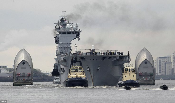 Welcome to London: The UK's largest warship HMS Ocean nudges its way through the Thames Barrier on it's way to docking at Greenwich, London.