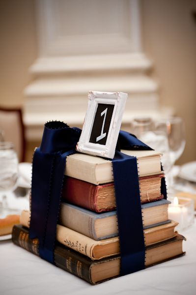 Instead of flowers on the table, collect vintage books that she wrapped in blue ribbon and topped off with a little frame showcasing the table number.