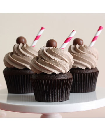 Each cupcake is topped with a sky-high mound of chocolate malt buttercream, a chocolate malt ball, and a paper straw.