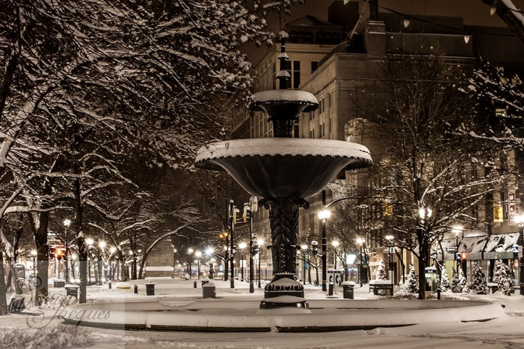Gore Park Fountain in the center of Hamilton Gore Park.  Connaught building in the background. Evening of Snow storm. Night image. Long exposure.