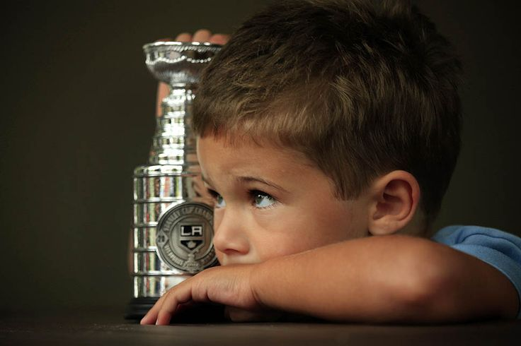 Jake Brown, son of Dustin Brown, hold a replica of the Stanley Cup at their home, via the Los Angeles Times