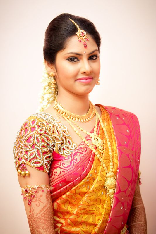 South Indian bride. Gold Indian bridal jewelry.Temple jewelry. Jhumkis. Pink and yellow silk kanchipuram sari with cut work blouse.Braid with fresh flowers. Tamil bride. Telugu bride. Kannada bride. Hindu bride. Malayalee bride.Kerala bride.South Indian wedding.