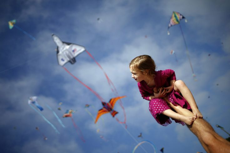 Madeleine Klonoski, 2, sits on her father's leg at a kite festival in Redondo Beach, California, on March 8, 2015.
