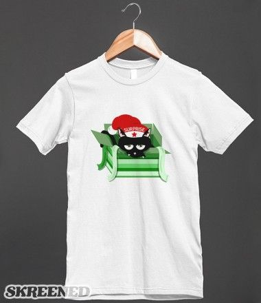 t-shirt Naughty Cat Surprise Present  | A surly looking cat who has climbed into a christmas present box. The cat is wearing a red santa hat. The slogan reads surprise. #Skreened
