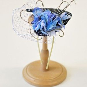 blue and white polka dot cotton fabric in a heart shaped base, decorated with blue fabric flowers, violet veil and details of peacock feathers. - See more at: www.whereisthecat...