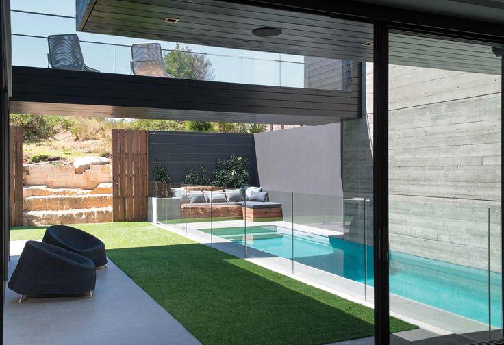 Le patio de cette maison de ville avec la piscine, la terrasse et le gazon vert