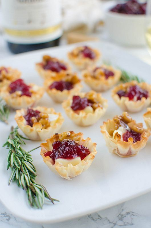 Msg 4 21+ Cranberry Brie Bites - a quick and easy holiday appetizer! Melted brie and cranberry sauce in crisp phyllo cups with candied walnuts on top!