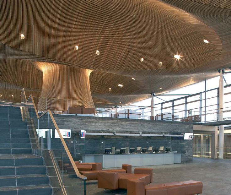 """National Assembly for Wales"": An undulating roof made of bent timbers seems to grow from the center of the Wales Assembly like a tree, hovering over the entire glassed space. The form reinforces notions of transparency and regeneration, a key goal of the program.   