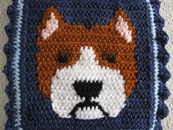 Handmade, pit bull dog pot holder set. Pot holders are an original crochet design featuring red fawn and white pitbull dogs against a denim blue background. The Am staff terriers are crocheted with white and rust and have light pink ears. The eye is walnut brown with black centers. Pot